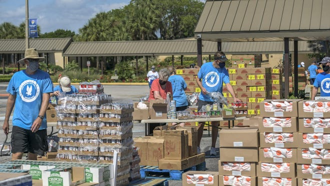 People prepare groceries for distribution at a food drop at Lake-Sumter State College in Leesburg on Thursday, May 21, 2020.