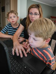 Karen McLean coaches her son, Marcus, 5, as he works