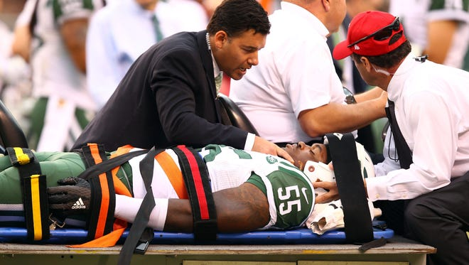 New York Jets linebacker and former University of Louisville player Lorenzo Mauldin is carted off the field on a stretcher with team doctors during a game this past September.