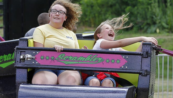 Marie Cole, 18, left, and sister, Patience Card, 10, both of the Town of Nichols, ride the scrambler during the 2016 Tioga County Fair.