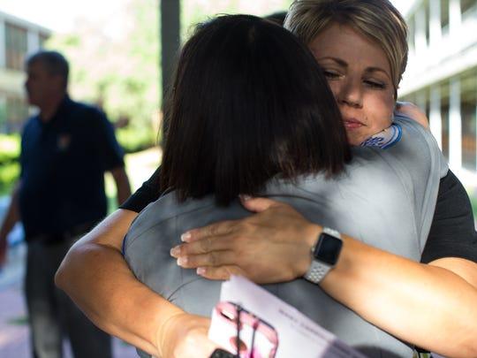A security guard at Carroll High school hugs Principal