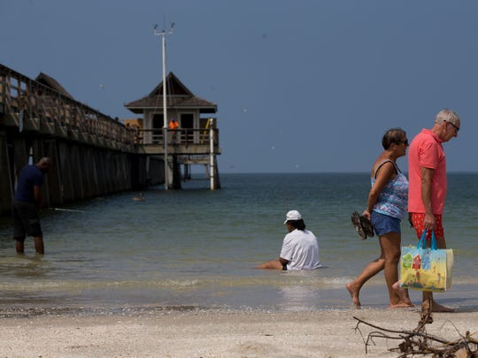 Beach visitors walk along the sand as, almost two weeks after Hurricane Irma made landfall, the Naples Pier was re-opened, albeit only half, to the public midday Thursday, Sept. 21, 2017 in Naples. Further assessment of the second half of the Pier is required to determine the extent of the damage after a guardrail at the end of the pier blew off in the storm.