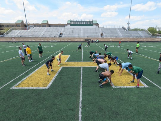 Players take part in an  athletic conditioning class on the Farmington Hills Harrison football field last week.