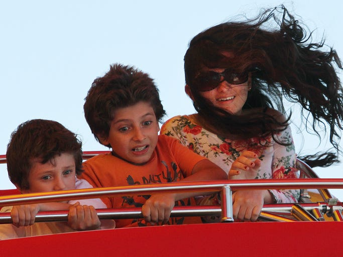 ASB 0825 Seaside Heights  The DeLorenzo children of Toms River, react while taking a ride on the Musik Express ride on the boardwalk in Seaside Heights, Sunday, August 24, 2014. From left are: Ricky, 6, Nicholas, 10, and Dalia, 15. The family came out to celebrate Nicholas' tenth birthday. Mary Frank/Staff Photographer