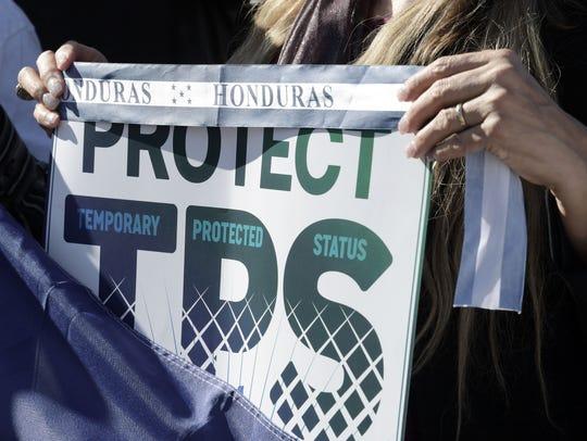 """Una mujer sostiene una pancarta que dice """"Proteja TPS"""","""