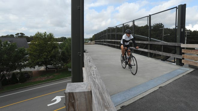 A cyclist heads over the Cape Cod Rail Trail's overpass bridge on Station Avenue in South Yarmouth. The third phase of trail's extension will run from Peter Homer Park to Higgins Crowell Road.