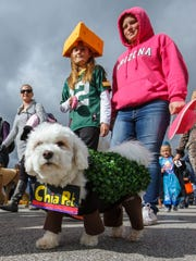 "Ashley Anderson (center), 11, and Cheyenne Kaatz (right), both of Pewaukee, walk in the costume parade during Pewaukee's 2015 Halloween Fun Fest.. Anderson won the dog costume contest with her pup named ""Shadow"" dressed as a Chia Pet. This year's Fun Fest in Pewaukee is slated for  noon to 1:30 p.m. Saturday, Oct. 21."
