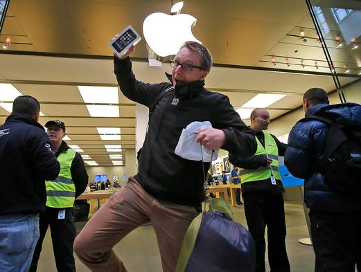 A customer celebrates his purchase of a new iPhone 5S as he leaves the Apple store on Sept. 20 in Oberhausen, Germany. The new iPhone 5s and 5C went on sale today around the world.