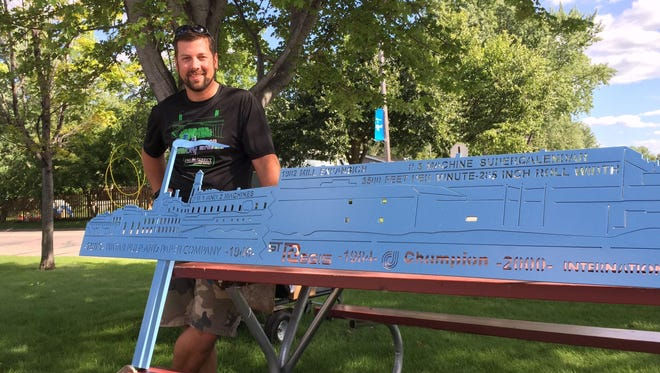 Sartell High School technology teacher Joe Schulte poses Monday with one of the pieces built as part of the Sartell Mill Public Art Project at the Sartell Farmers Market.