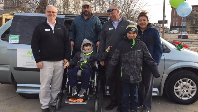 The Figueroa family poses with employees of Mobility Works of Waukesha after taking delivery of their new wheelchair-accessible van on Tuesday. Pictured are general manager Mike Harty (clockwise from left), Jose Figueroa, salesman Brian Williams, Imelda Figueroa and Daniel and David Figueroa.