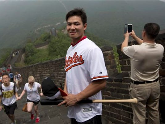 Chinese baseball player Xu Guiyan, wearing a Baltimore Orioles team jersey, looks on as he poses at the Mutianyu section of the Great Wall of China in Beijing on Thursday. The hardest part for Xu Guiyan about signing with the Orioles was keeping it a secret. The 19-year-old Xu this week became the first player from one of the MLB's three development centers in China to sign with a major league club.