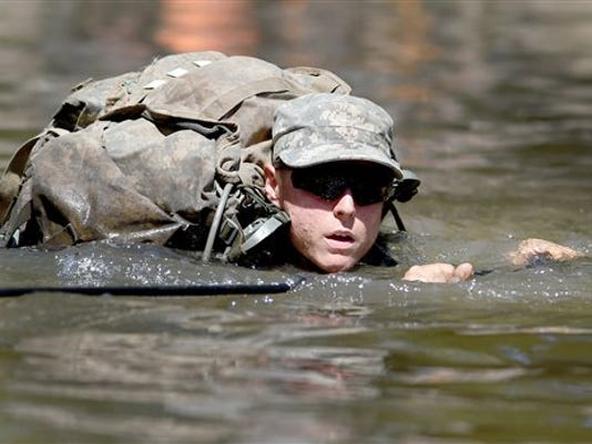 A female Army Ranger student crosses the Yellow River on a rope bridge on Tuesday, Aug. 4, 2015, at Camp James E. Rudder on Eglin Air Force Base, Fla. Two out of 19 females have made it to the final phase of Army Ranger training which ends at Camp James E. Rudder on Eglin Air Force Base. Pentagon leaders decided in 2013 to investigate the possibility of opening all military jobs to women.