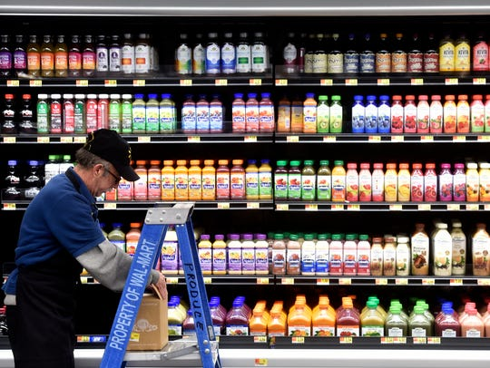Jim Corbally, a produce sales associate at Wal-Mart, restocks juices on Wednesday at the 10th Avenue South Wal-Mart.
