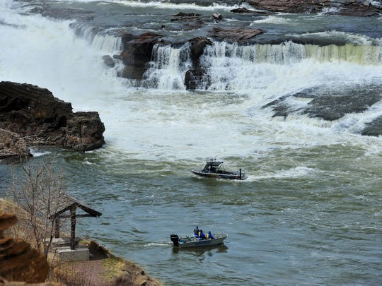A boat from the Cascade County Sheriff's Office aided by a boat from Cascade County Search and Rescue patrol the waters below Black Eagle Falls at Black Eagle Dam as they search for Brittney Roberts, who was washed over the dam.