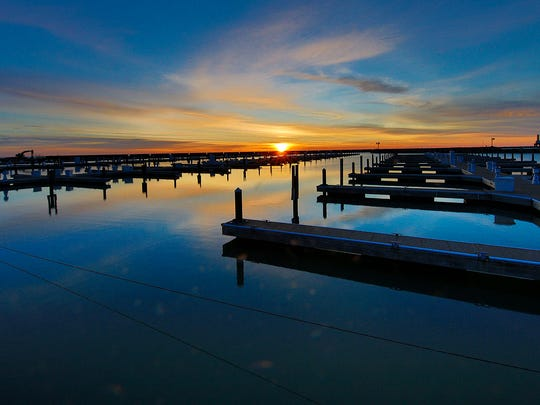 The sun rises over the marina in Port Washington in
