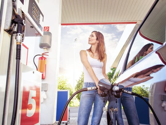 A young woman fills her vehicle at a gas station.