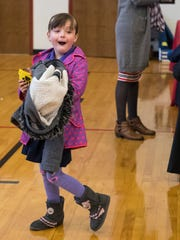 Second-grader Lilith Elsa, 7, reacts happily to a Sylvester the Cat mascot while holding a new coat in her hands during the Coat-A-Kid Kickoff event at Glenwood Leadership Academy in Evansville, Ind., Tuesday, Oct. 24, 2017. From October through December, Don's Claytons DCI Fine DryCleaning will be collecting gently used and new coats from the community to distribute to children in need.