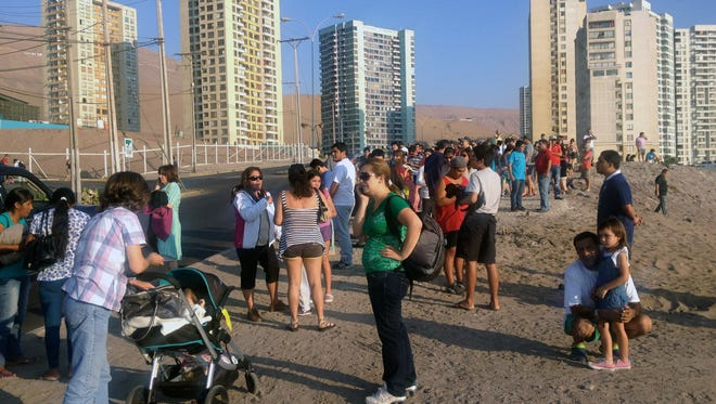 People wait in high areas after hearing a tsunami alert following a quake in Iquique, 1800 km north of Santiago, Chile, on March 16, 2014.