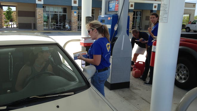 Space Coast Credit Union worker Jill Rosseau fills gas into one of the lucky motorists Friday to receive free gas.