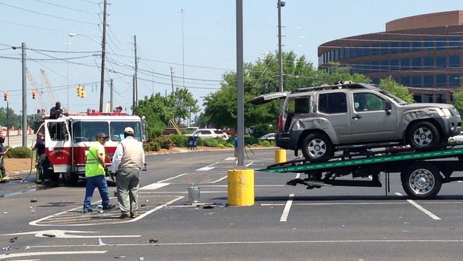SUV flips after colliding with a white minivan in the parking lot of Fresh Market off of Perry Hill Road Friday.