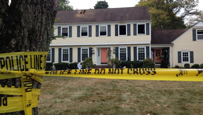 Police tape cordons off the Meadow Run Drive home Monday where the Sheridans were found.