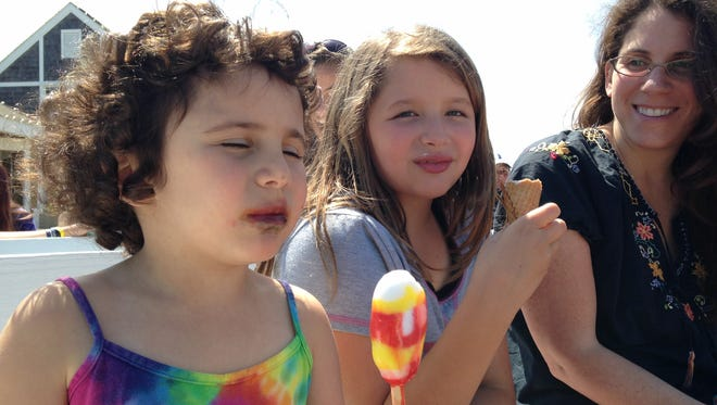 Eva Palanzo enjoys her Spongebob Squarepants Popsicle in front of the Bethany Beach bandstand on Saturday.