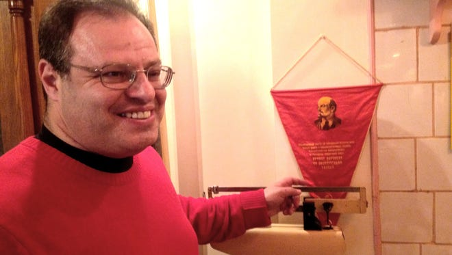 Arkady Milgram, 50, from Los Angeles, emigrated from the Soviet Union in 1988. He looks at memorabilia in the restaurant Petrovich in Moscow on Feb. 11, 2014. The red pendant is an old Communist Party banner featuring Lenin.