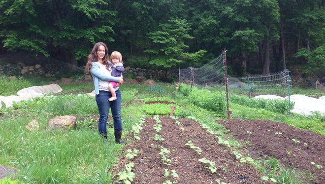 Jocelyn Apicello, with her daughter, beside a vegetable bed at Longhaul Farm, in Garrison, where she and her husband, Jason Angell, live and work.