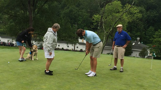 Eli Manning prepares to putt blindfolded at the Guiding Eyes For The Blind's 37th annual Golf Classic at Mount Kisco Country Club.
