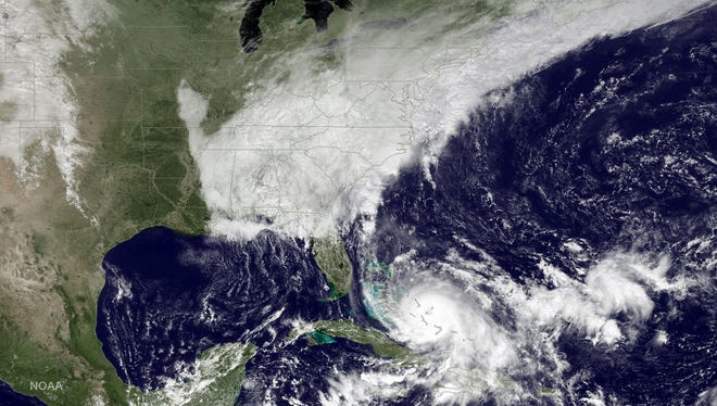 This satellite image taken Friday, Oct. 2, 2015 at 12:45 p.m. EDT, and released by the National Oceanic and Atmospheric Administration (NOAA), shows Hurricane Joaquin, bottom center, pounding the Bahamas and a deepening low pressure system on the U.S. east coast.
