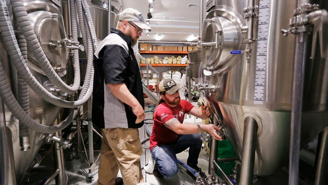 Brewer Jason Clark, left, looks on as Nick Maxson adjusts the racking arm on a fermenter before transferring the wort for California Common Ale Wednesday, May 16, 2018, at Teays River Brewing & Public House, 3000 S. Ninth Street, Suite A, in Lafayette.