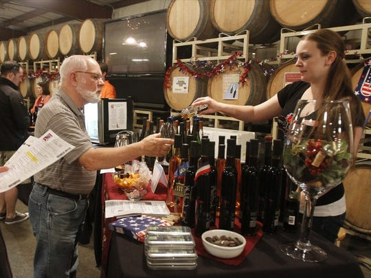 Emily Ferries, right, pours dessert wines for Don Moberg at Eola Hills Wine Cellars in 2012. Enjoy the winery's wine with dinner on Valentine's Day.