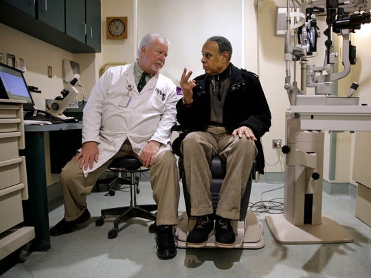 In this March 12, 2015 photo, optometrist Paul Archambault (left) talks with U.S. Army veteran Kenneth Chavis during a glaucoma examination at the Fayetteville Veterans Affairs Medical Center in Fayetteville, N.C.