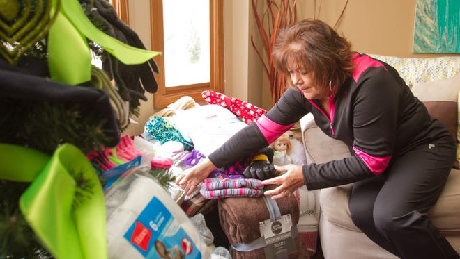 At her Marion Township home, Patty LaPradd arranges some of the blankets and socks she's collected to give to homeless people in Detroit. She also displayed some of the gloves and socks she'll give away in a Christmas tree, shown in the foreground.