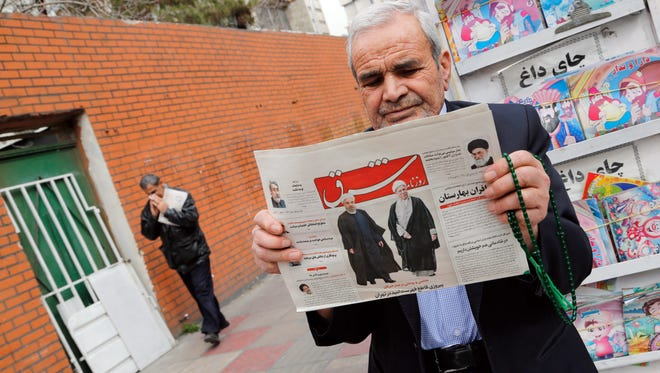 An Iranian man holds a copy of the daily 'Shargh' newspaper with pictures of Iranian President Hassan Rouhani and former president Akbar Hashemi Rafsanjani and headline reading 'Decisive victory for the reformist' outside a kiosk in Tehran on Feb. 28, 2016.