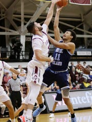 Fordham's Joseph Chartouny (12) defends Rhode Island's Jeff Dowtin (11) during the first half of an NCAA college basketball game Wednesday, Jan. 24, 2018, in New York. (AP Photo/Frank Franklin II)