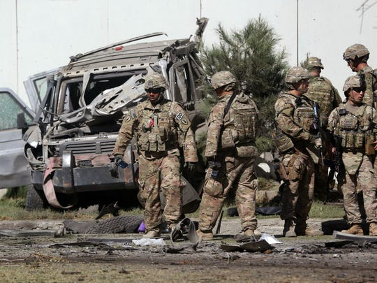 U.S. troops inspect the site of a suicide attack in Kabul, Afghanistan, in 2014. Some 2,400 U.S. servicemen and women have lost their lives during the 18-year U.S. presence in the region — the most recent in early September as the Taliban struck again and vowed to disrupt upcoming presidential elections.