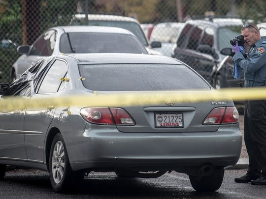 An Albuquerque police department crime scene investigator photographs a vehicle near a shooting site in Albuquerque, N.M. , Wednesday, Oct. 21, 2015. Police detained a man on Wednesday in connection with the road-rage killing of a 4-year-old girl who was shot in the backseat of her father's truck after he picked up her and her brother from school, signaling a possible break in a case that has horrified the public. (Roberto E. Rosales/The Albuquerque Journal via AP) MANDATORY CREDIT