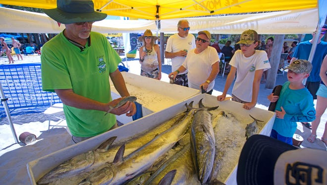 Robert Turpin talks about different species of fish Sunday, June 24, 2018 during the Bud Light Fishing Rodeo at Flounders at Quietwater Beach.