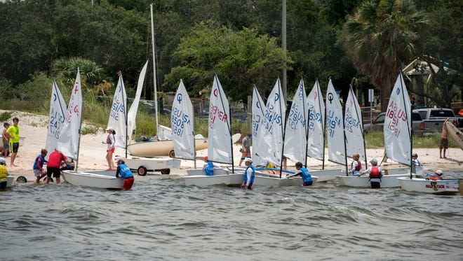 Young sailors bring their boats back to the Pensacola Yacht Club because of an incoming thunder storm during the Junior Olympic Sailing Festival Saturday, June 30, 2018.