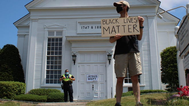 """Bryce Waldrop of York holds a """"Black Lives Matter"""" sign that he made with plywood during a demonstration Saturday, June 6, along York Street in York, Maine. """"I wanted something durable that would hold up and maybe use it again or reflect on it later,"""" Waldrop said."""
