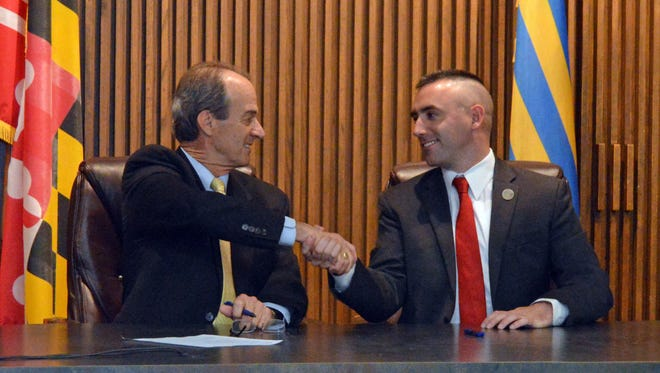 Wicomico County Executive Bob Culver, left, and Salisbury Mayor Jake Day shake hands after signing agreements between the city and county on Monday, Dec. 12.