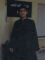 Akram I. Musleh in front of the ISIL flag he purchased