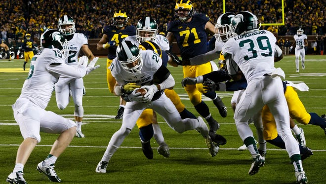 Michigan State Spartans defensive back Jalen Watts-Jackson dives into the end zone for a game winning touchdown as the clock runs out in the fourth quarter against the Michigan Wolverines at Michigan Stadium.