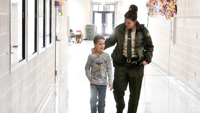 "Deputy Jamie Haynes walks the halls with her ""Deputy of the Day"" Ben Spradlin. Haynes is the School Resource Officer at Franklin Elementary. Five years ago, county officials rushed to staff all elementary schools with SROs following the Sandy Hook tragedy. 