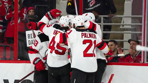 New Jersey Devils forward Nico Hischier (13) is congratulated by forward Kyle Palmieri (21) and defenseman Sami Vatanen (45) after scoring a first period goal against the Carolina Hurricanes at PNC Arena.