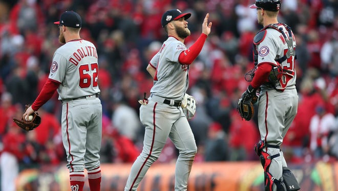 Washington Nationals right fielder Bryce Harper (34) high fives teammates after the 2-0 win against the Cincinnati Reds on Opening Day, Friday, March 30, 2018, at Great American Ball Park in Cincinnati. The Washington Nationals won 2-0.
