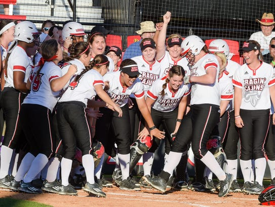 Kelsey Vincent  is greeted a home plate after one of