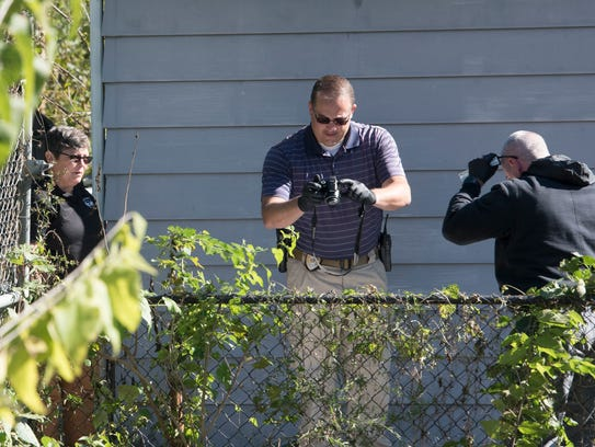 Officials take photos and collect evidence from a body