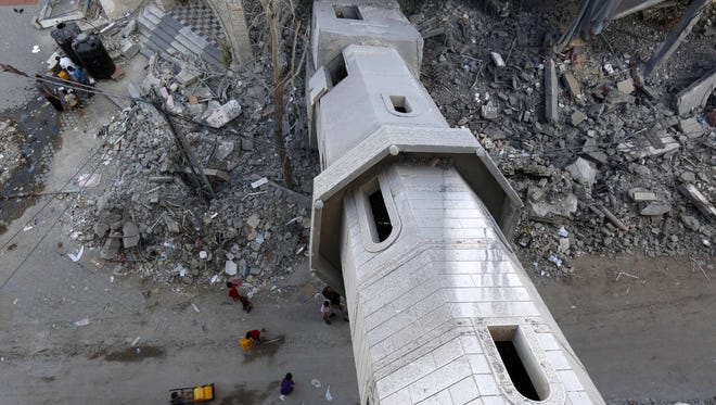 Palestinians walk under the collapsed minaret of a mosque in Gaza city on August 8, 2014, that was destroyed during the Israeli offensive on the Gaza Strip. Israeli warplanes pounded targets across Gaza, where two Palestinians were killed and militants fired dozens of rockets into Israel after renewed hostilities ruptured a fledgling three-day truce.